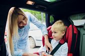 Family, Transport, Road Trip And People Concept - Happy Woman Fastening Child With Safety Seat Belt  poster