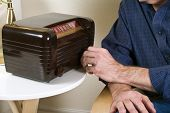 foto of olden days  - A man turning the knob on an old fashioned radio - JPG