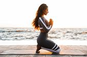 Photo of strong young fitness woman outdoors in the beach make yoga meditate exercises. poster