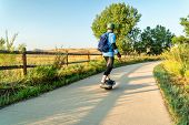 An adult man is riding an electric skateboard on the Poudre River Trail in northern Colorado.It is a poster