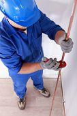Tradesman using a tool to shape a cooper tube