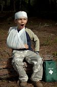 picture of sling bag  - First Aid treatment given to a young boy in the forest showing an arm sling and a head injury - JPG