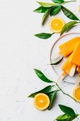 Homemade Orange Ice Cream On Stick. White Background With Orange Fruits Slices And Orange Tree Leave poster