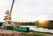 The Port Crane Makes Loading Of Wood Chips Into The Freight Cars Of The Train, Loading, The Sun poster