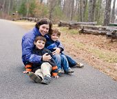 stock photo of heartwarming  - Thirtysomething mom sitting in driveway with preschool sons in winter - JPG