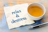 relax and distress note  - handwriting on a napkin with a cup of green tea poster