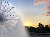 A Fountain Spraying Mist As The Sun Sets poster