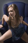 stock photo of risque  - sultry brunette in sexy dress rising out of armchair - JPG