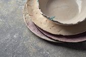 Decorative pottery - bowls, plates covered with glazed on a gray background. Traditional decorative  poster