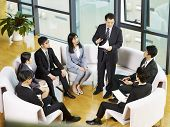 Boss Speaking To Team Of Asian Business People Sitting In A Circle During Meeting In Office. poster