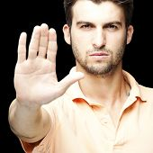 portrait of young man doing stop symbol over black background