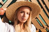 Portrait of attractive young blond woman 20s in straw hat and swimwear posing against wooden beams o poster