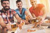 Young Smiling Men Drink Beer And Eat Pizza At Home. Friends On Party. Weekend At Home. Three Happy F poster