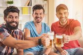 Three Young Men Drinking Beer On Party At Home. Friendship Concepts. Drinking Beer. Smiling Young Ma poster