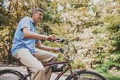 Old Man Sitting On Bicycle In Park In Summer. Healthcare Concept. Relaxing In Park. Active Rest Conc poster