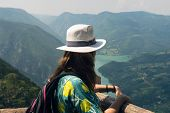 Girl Relaxing On A Beautiful Mountain View. Traveler Standing On Mountain Rock Enjoying Beautiful Mo poster