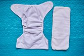 White Cloth Diaper With Insert Lay On Bed Blanket poster