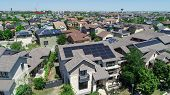 Suburbs And Suburban Facades And Hundreds Of Solar Panel Rooftops And Homes Wrapped Around Green Lan poster