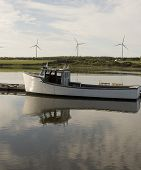 stock photo of lobster boat  - Wooden lobster boat with windmills in the background