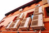 stock photo of air conditioner  - Air conditioner on the exterior of an orange building - JPG
