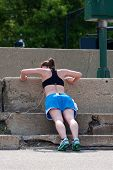 Young Woman Does Pushups Against Concrete Steps In Urban Setting