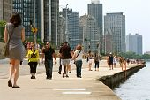 People Enjoying Being Active Along Chicago Shoreline On Lake Michigan