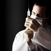 Male Doctor With Needle Syringe On Dark Background