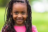 stock photo of innocence  - Outdoor close up portrait of a cute young black girl smiling  - JPG