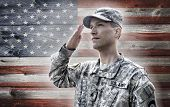 stock photo of camouflage  - Army soldier saluting on the grunge american flag background - JPG
