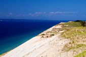 foto of dune  - Steep sand dunes rise out of Lake Michigan at Sleeping Bear Dunes on a bright sunny day with a few summery clouds - JPG