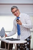 Businessman text messaging while ironing pants
