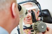 Senior woman sitting behind slit lamp at optician