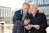 Happy senior couple with map and city guide app on smartphone