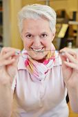 Elderly smiling optician with new glasses in her hand