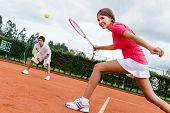 image of sportive  - Woman playing doubles in tennis at a clay court - JPG