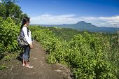picture of filipina  - filipina girl looking at taal volcano crater lake from trail along rim near manila in the philippines - JPG