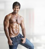 stock photo of hunk  - Sexy smiling shirtless male model with muscular body and abs against white background - JPG