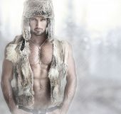 Fashion portrait of a beautiful male model in fur hat and vest against modern background with copy s