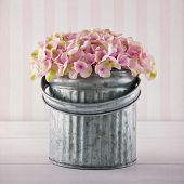 stock photo of bucket  - Pink hydrangea flowers in a metal bucket on vintage striped background - JPG