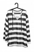 A studio shot of a black and white striped prison uniform on a hanger isolated against white background