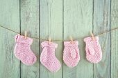 stock photo of clotheslines  - Pink baby girl socks and mittens on vintage clothesline on green vintage wooden background - JPG