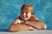 Resto de niño en su codo en el borde de la piscina