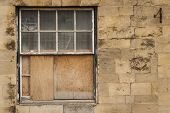 Old wooden sash window half boarded up