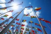 stock photo of geography  - Flags of all nations of the world are flying in blue sunny sky - JPG