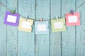 stock photo of clotheslines  - Five empty colorful photo frames or notes paper hanging with clothespins on wooden blue vintage shabby chic background - JPG