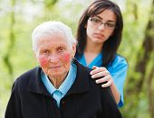 picture of empathy  - Sad elderly woman and caring nurse outdoors - JPG