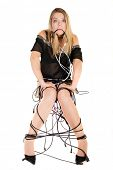 Woman sitting and chained with electric cables