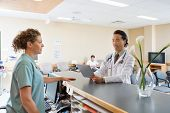 stock photo of reception-area  - Nurse and doctor with digital tablet conversing at hospital reception - JPG