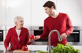pic of grandma  - Grandma and grandson are preparing meal together at home - JPG