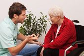 stock photo of hospice  - Nurse keeping company to disabled elderly lonley person - JPG